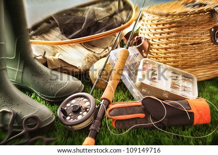 Boots and fly fishing equipment on grass - stock photo