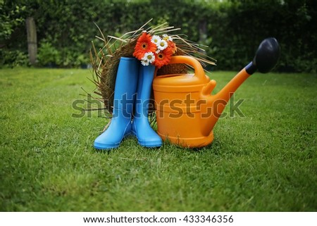 boots with watering can on grass