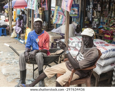 BOR, SOUTH SUDAN-OCTOBER 30, 2013: Unidentified men sell their goods at an outdoor market in Bor, South Sudan - stock photo
