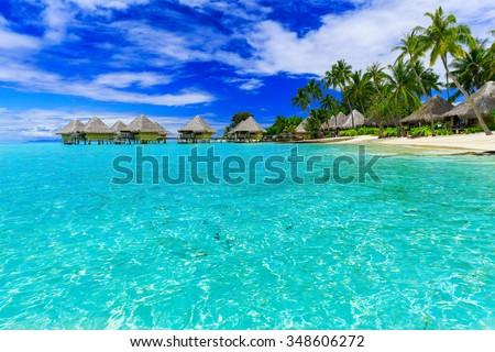 Bora Bora, French Polynesia. Over water bungalows palm trees and beach. - stock photo