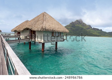 BORA BORA - JANUARY 24, 2015: World famous holiday destination Bora Bora and Tahiti  are a part of French Polynesia. Over-water bungalows are posed in blue-green waters of South Pacific Ocean. - stock photo