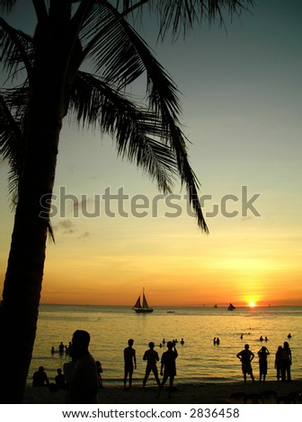 Boracay, Philippines Sunset with Palm Tree and People - stock photo