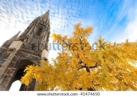 Bordeaux cathedral spire behind gingko tree with yellow leaves. - stock photo
