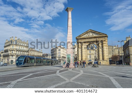 Bordeaux, France - March 26, 2016. Tram rolling near to Porte d'Aquitaine (local name) Aquitaine gate at Place de la Victoire. To the left the monument to the wine. Bordeaux, France. - stock photo