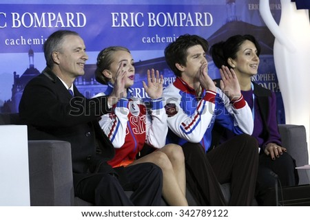 BORDEAUX, FRANCE - NOVEMBER 13, 2015: Coach SVININ (L), skaters STEPANOVA / BUKIN and coach ZHUK  wait for the score after short dance at Trophee Bompard ISU Grand Prix at Patinoire Meriadeck Arena. - stock photo