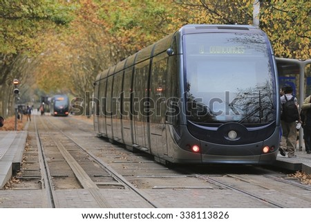 BORDEAUX, FRANCE- October 5 2015: Tram is passing by the Place des Quinconces and colorful autumn trees in Bordeaux, France - stock photo