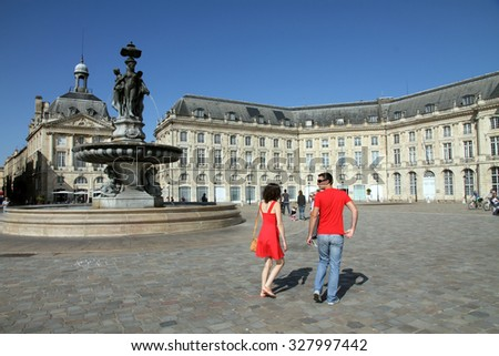 BORDEAUX, FRANCE - SEPTEMBER 5: People walks on the Place de la Bourse.  The fountain of Three Graces in the center of square was erected in 1869. - stock photo