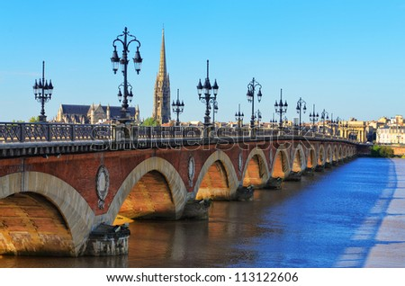 Bordeaux river bridge with St Michel cathedral - stock photo
