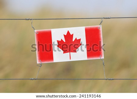 Border fence - Old plastic sign with a flag - Canada - stock photo