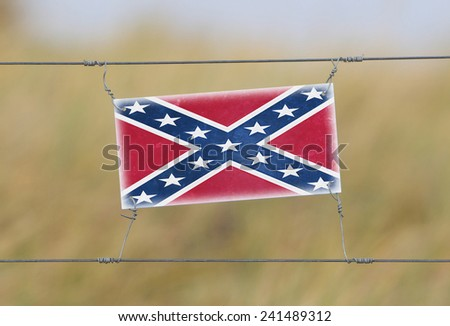 Border fence - Old plastic sign with a flag - Confederate flag - stock photo