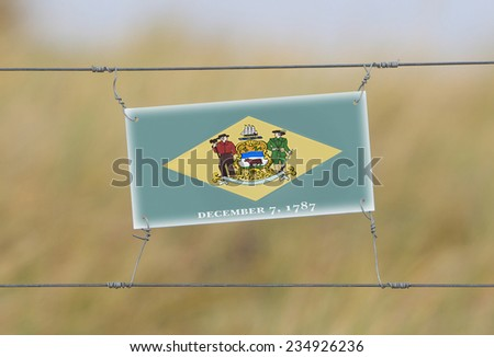 Border fence - Old plastic sign with a flag - Delaware - stock photo