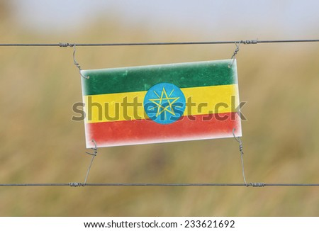 Border fence - Old plastic sign with a flag - Ethiopia - stock photo