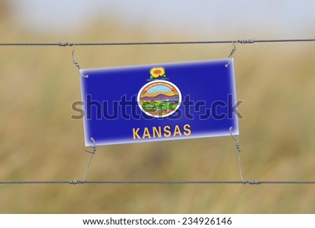 Border fence - Old plastic sign with a flag - Kansas - stock photo