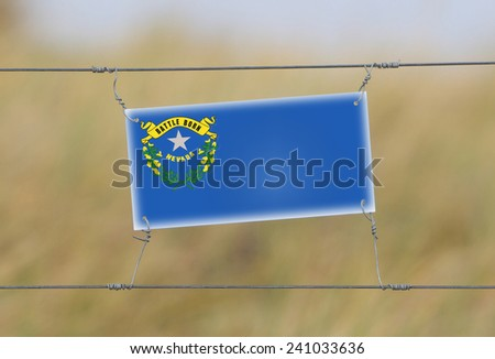 Border fence - Old plastic sign with a flag - Nevada - stock photo