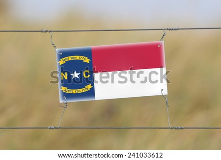 Border fence - Old plastic sign with a flag - North Carolina - stock photo