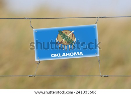 Border fence - Old plastic sign with a flag - Oklahoma - stock photo