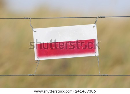 Border fence - Old plastic sign with a flag - Poland - stock photo