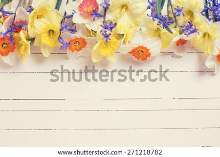 Border from colorful yellow, orange and blue spring flowers  on white  painted wooden planks. Selective focus. Place for text. Toned image. - stock photo