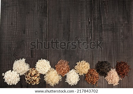 Border made of  assortment whole grain rice in a rustic wooden surface background - stock photo
