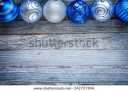 Border of Christmas balls on top of an old wooden board, copy space for text, top view.