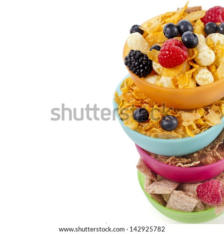 Border of corn flakes in colorful plastic bowl with fresh berries isolated on white background