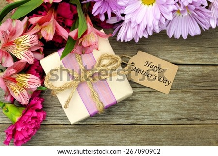 Border of flowers with Mother's Day gift box and tag against a rustic wood background - stock photo