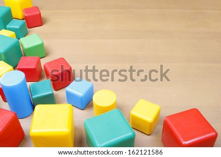 Border of the colorful plastic blocks on wooden background - stock photo