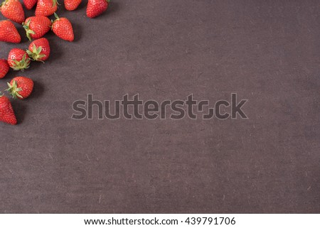 Border of whole fresh ripe red strawberries arranged on left sides on a dark textured slate background with copyspace. Berry frame with copy space on right. Strawberries, dark wood background.  - stock photo