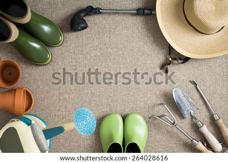 Border or frame of gardening tools on a neutral beige textile background with garden shoes and boots, sunhat, watering can, hand tools and flowerpots, with central copyspace, view from above - stock photo