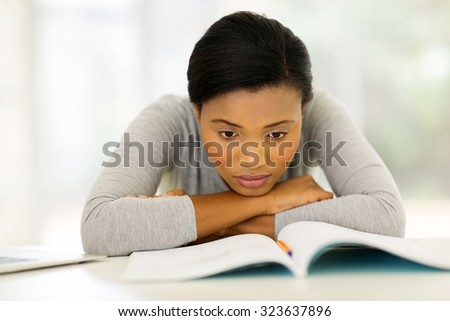 bored american university student lying on desk - stock photo