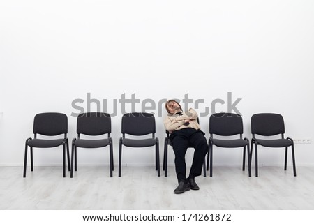 Bored and disappointed employee sitting in waiting room on a row of chairs - stock photo