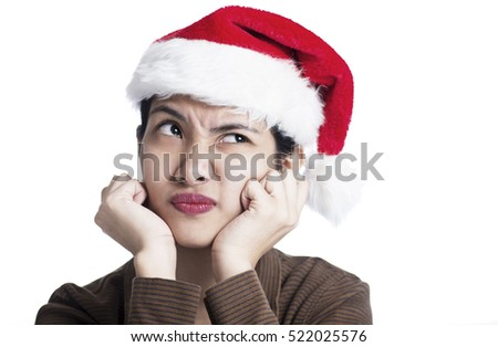 Bored and pensive lady wearing a Santa hat. Isolated in white background.