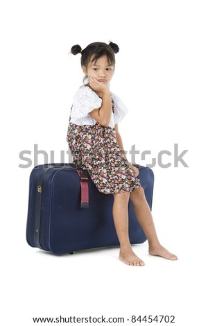 bored Asian girl sitting on her luggage over white background - stock photo