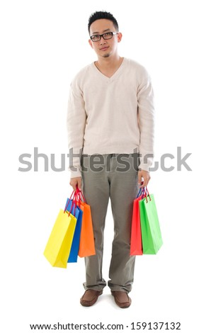 Bored Asian man shopper holding shopping bags waiting for his girlfriend standing isolated over white background - stock photo