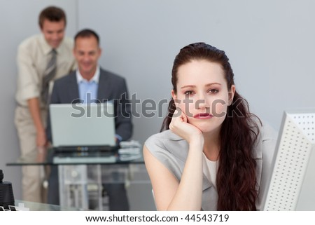 Bored attractive businesswoman looking at the camera - stock photo