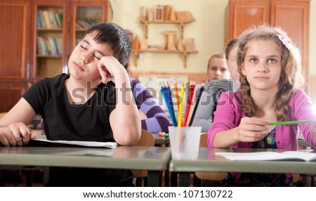 Bored boy sleeping and dreaming during a lesson in classroom - stock photo