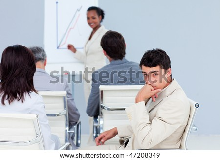 Bored businessman at a conference with his colleagues - stock photo