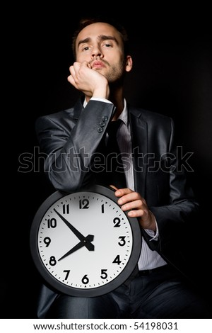 bored businessman holding clock, over black - stock photo