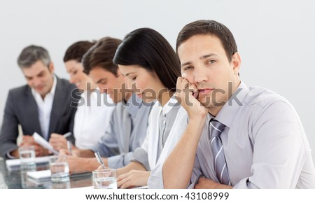 Bored businessman in a meeting with his team - stock photo