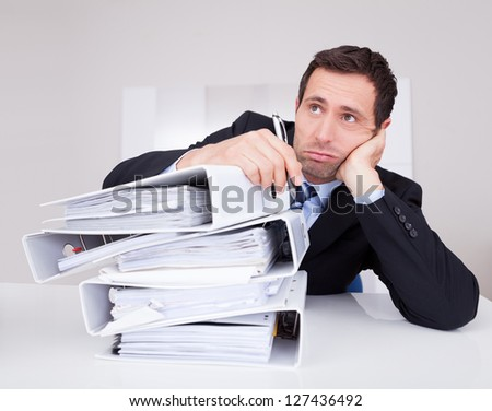 Bored Businessman Overwhelmed By Paperwork In The Office - stock photo