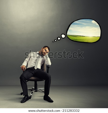 bored businessman sitting on the chair with speech bubble and thinking about rest over grey background - stock photo