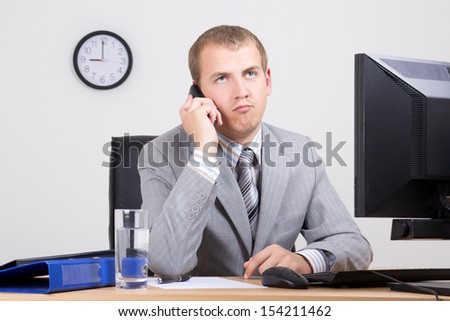 bored businessman talking on phone in his office - stock photo