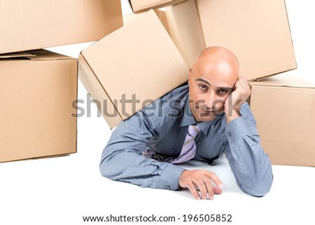 Bored businessman under a pile of cardboard boxes