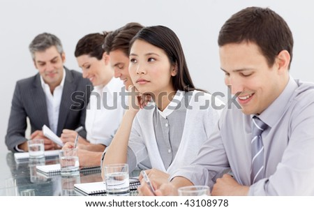 Bored businesswoman at a conference with her team - stock photo