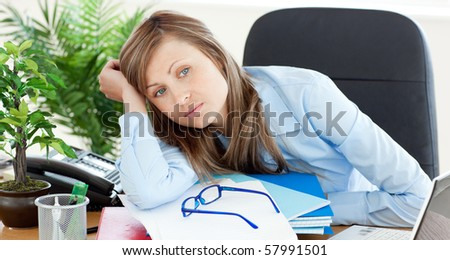 Bored businesswoman sitting at her desk in her office