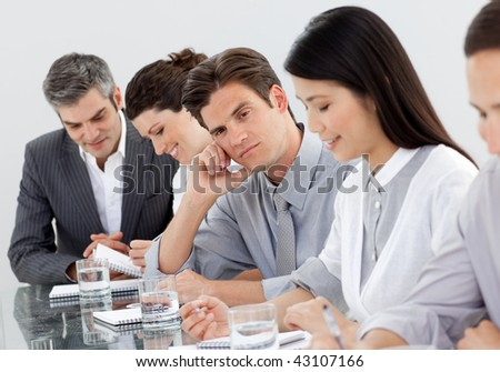 Bored caucasian businessman at a presentation with his colleagues - stock photo
