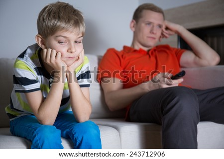 Bored child sitting on the sofa and his father watching tv - stock photo