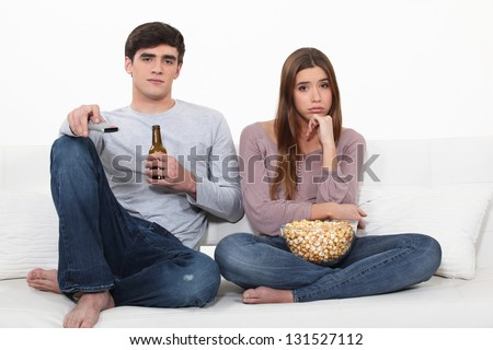Bored couple watching TV - stock photo
