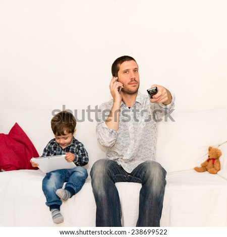 Bored father making a phone call and watching tv while baby is playing with tablet on a white sofa with a red pillow and a bear toy - stock photo
