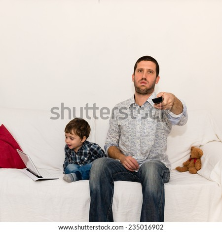 Bored father watching tv with a smile baby playing with tablet - stock photo